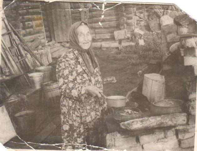 Фото 1986, в Старейшей Нягани первожитель Хаймазова Евгения Матвеевна около своего дома у печки